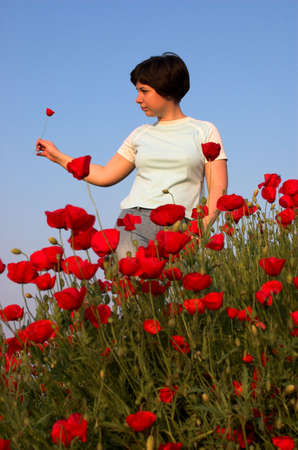 Girl on the poppies field and blue sky 3 photo