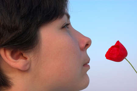beautiful girl watching stare on the red poppy photo