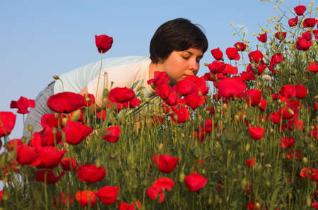 smells: Handsome girl smells poppies, Greece, Halkidiki Stock Photo