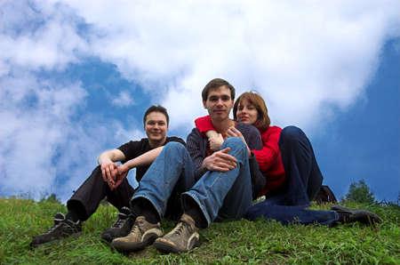 Three friends sitting on the grass