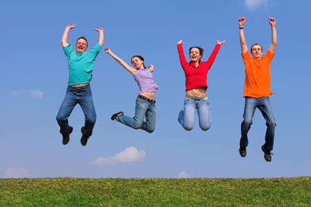 Four young people with color packets on green gras Stock Photo