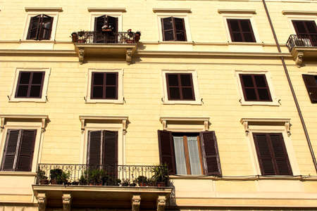 Vivid yellow  front of building with brown  shutters in Rome Stock Photo - 1808208