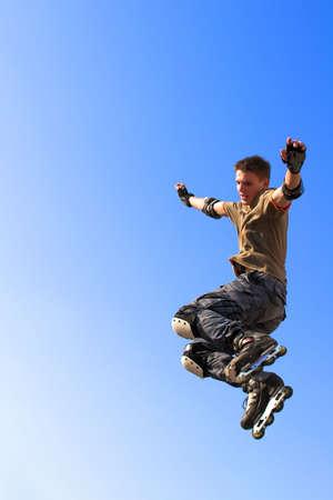 ni�o saltando: Active rodillo chico saltando de parapeto en el cielo azul
