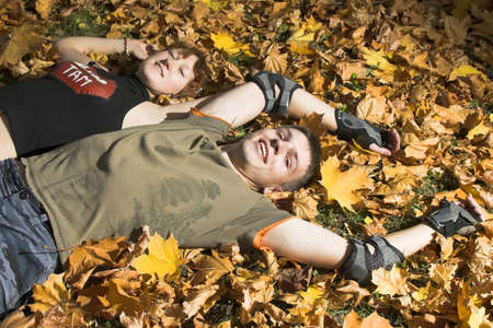 young couple lies on yellow leaves  Stock Photo - 2034069