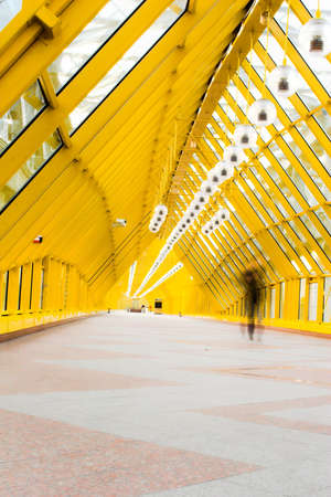 Yellow glass corridor in bridge and people walking photo