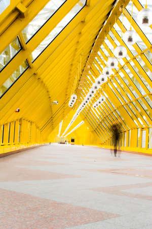 Yellow glass corridor in bridge and people walking photo