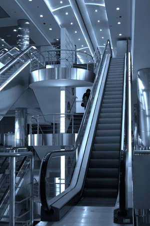 Free diagonal escalators stairway in center and ceiling lamps
