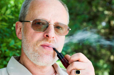 Adult man with glasses and wooden pipe photo