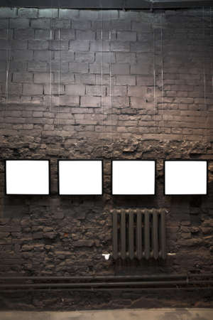 Four empty frames on brick wall in museum photo