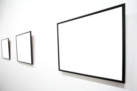 cadre: Three empty frames on white wall in museum