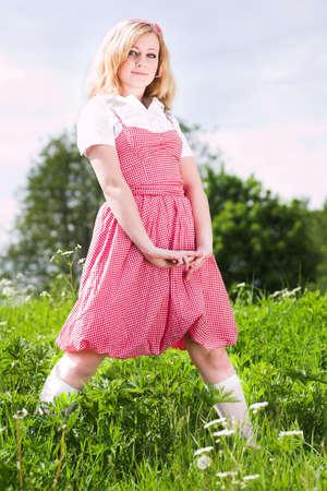 stay beautiful: Chica rubia hermosa estancia en rojo en verde prado  Foto de archivo