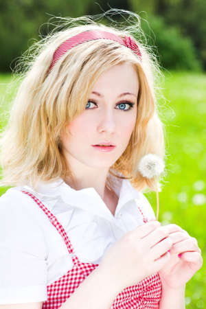 Wondered blonde beautiful girl portrait with dandelion photo