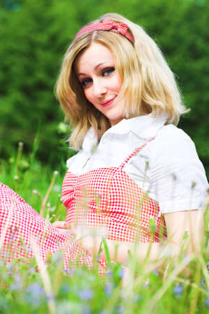 Blonde attractive girl sit on grass in park photo