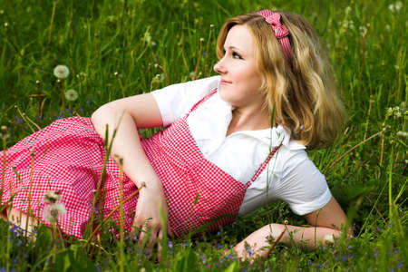 Beautiful country girl in red lay on grass photo