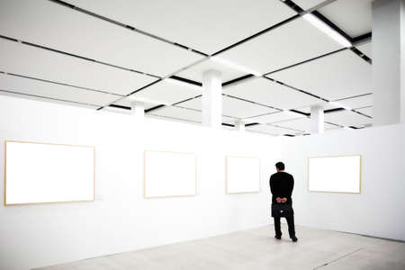 walls in museum with empty frames and person looking photo