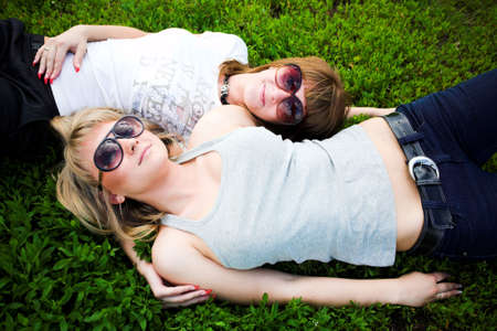 Two girls in sunglasses lay on green grass photo