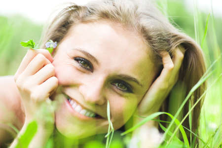 Girl lays on grass with flowers photo