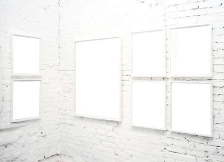 blank canvas: brick wall in museum with empty frames Stock Photo