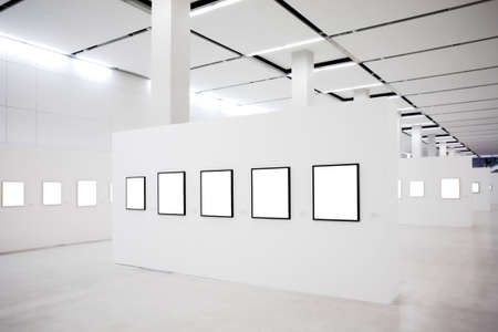 Exhibition in museum with many empty frames on white walls photo