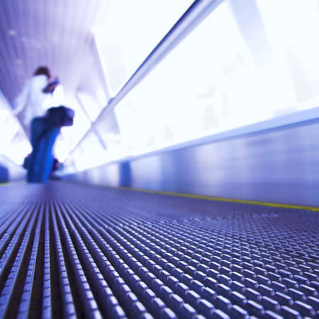 metallic stairs: Blue moving escalator in the office hall perspective view Stock Photo