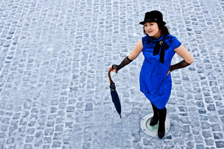 Oriental girl stay with umbrella on cobblestone road photo