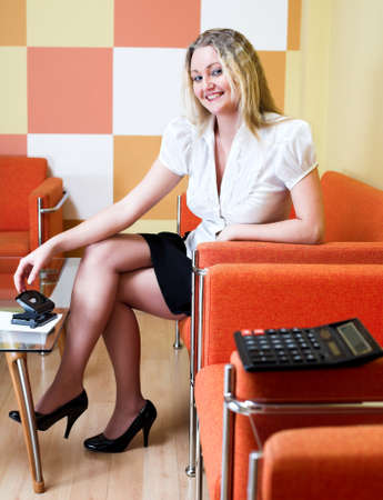 Woman in white sit at sofa in office photo