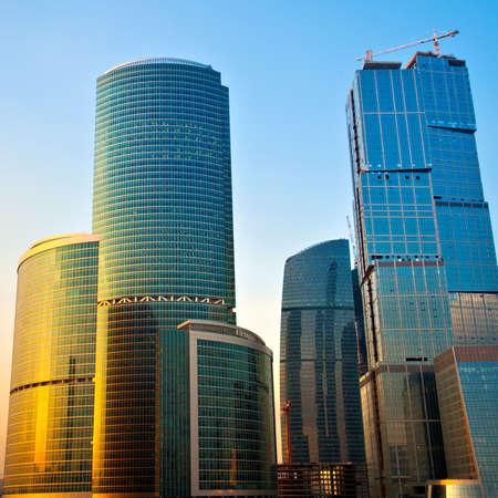 edificio cristal: Nuevos rascacielos en el centro de negocios de la noche, reflejos de oro