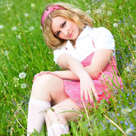 Smile beautiful country girl in red lay on grass photo