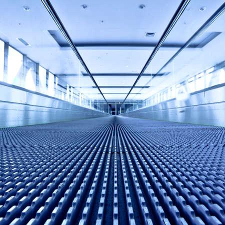 Escalator view in blue corridor in office centre, square composition photo