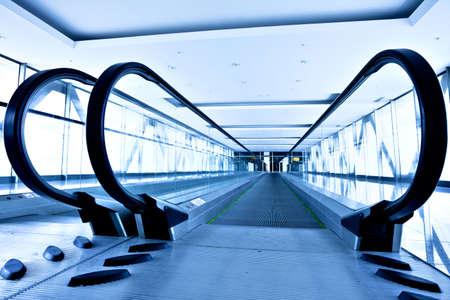 Empty gray escalator view in blue corridor in office centre photo