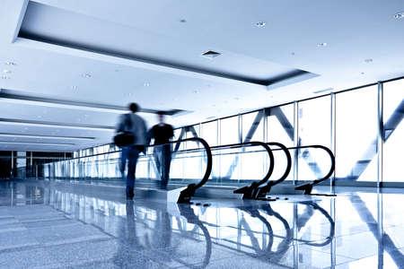 Two person move in grey corridor with escalators in office centre