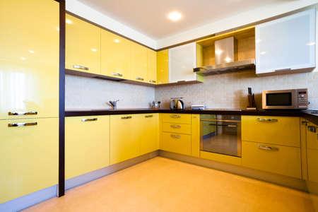 Yellow kitchen interior in modern flat