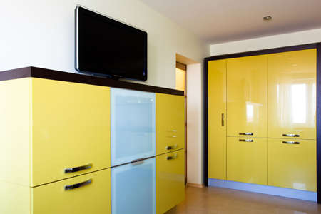 Corner in modern studio with TV and yellow bookcases Stock Photo - 4762727