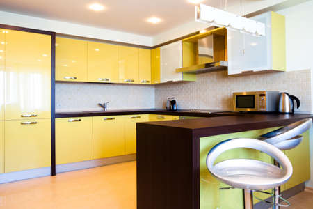 Yellow kitchen interior with chairs in modern flat