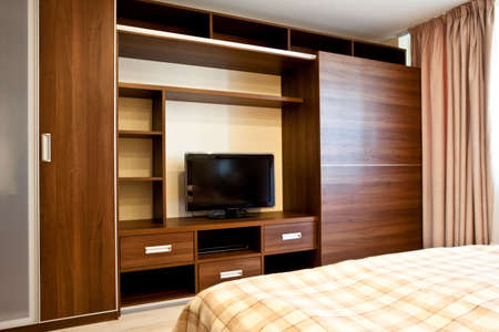 Comfortable bedroom with TV and wardrobes Stock Photo