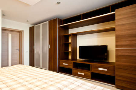built: Comfortable bedroom with TV and wardrobes Stock Photo