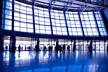 People in wide violet enter hall window in exposition center, left copmosition