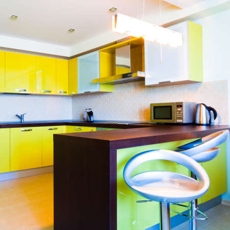Yellow kitchen interior with chairs in modern flat,square composition photo