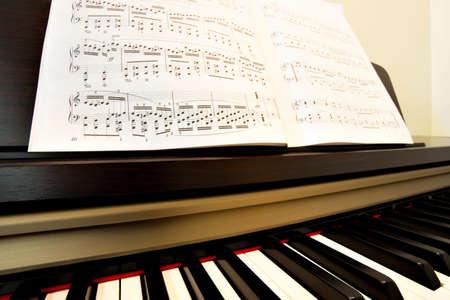 Piano keys and music paper close-up photo