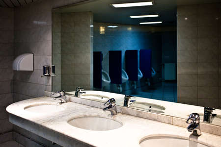 Empty restroom interior with washstands and toillets in mirror Stock Photo