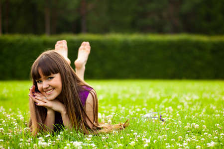 Pretty smiling girl with long brown hairs is laying on green grass photo