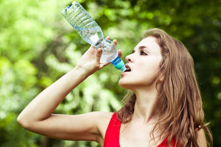 Girl drink water in park after sport Stock Photo - 5339994