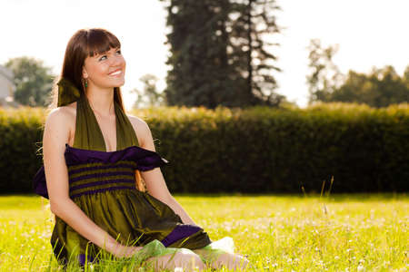 Pretty smiling girl is sitting on the grass in park photo