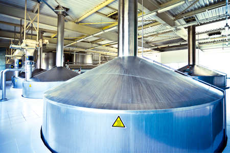 brewery: On the territory of brewers plant, view to blue steel fermentation vats