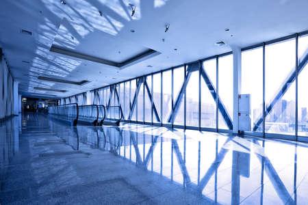 Glass corridor with blue escalator