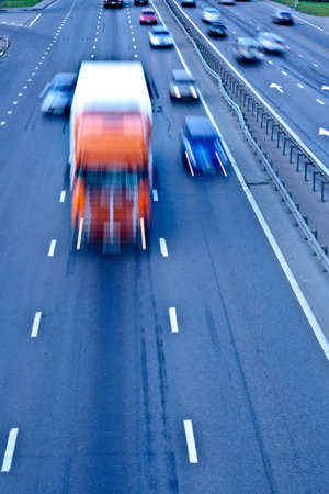 fast lane: Traffic road with orange truck, motion blur Stock Photo