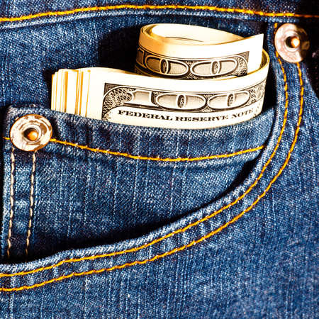 Jeans pocket with many one hundred dollar banknotes in roll photo