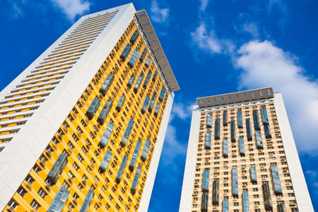 New yellow dwelling towers with balconies against blue sky photo