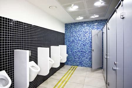 public housing: View to public toilet with grey cubicles and white urinals Stock Photo