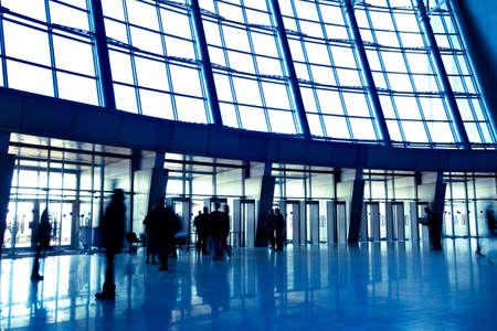 beursvloer: Mensen in grote blauwe zaal betreden venster expositie centrum, links copmosition Stockfoto